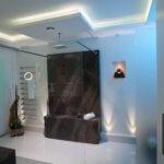 Lichtdesign badezimmer licht Schönes Licht im Badvola Das Badzubehör Design von Vola, das sich im Vola Handtuchhalter, der Vola Armatur, dem Vola Badheizkörper und der Vola Kopfbrause manifestiert, orientiert sich an der industriellen Badkultur, die insbesondere durch die indirekte Beleuchtung durch LED RGB hinter der Wand- und Deckenbespannung optimal zur Geltung kommt. Der Naturstein Waschtisch ist mit zwei schlichten Wasserhähnen von Vola Edelstahl gebürstet ausgestattet. Die Vola Armatur am Waschbecken harmoniert mit dem dazu passenden Vola Handtuchhalter. Für ein angenehmes Raumklima im Designer Bad sorgt der unauffällige Vola Badheizkörper, der beim Badezimmer planen selbstverständlich mitberücksichtigt wurde. Das Licht im Bad spielt auch hier eine entscheidende Rolle bei der Badezimmer Design Badgestaltung für exklusive Designbäder. Der Badezimmerplaner teilte bei der Umsetzung im Designerbad das Licht im Bad auf: LED Flächenlicht ist hier genauso zu finden wie Lichtvoute und eine hinterleuchtete Wand. Hinter der Wand- und Deckenbespannung verbirgt sich indirekte Beleuchtung, die mittels Lichtvoute für sanftes Licht sorgt. Einzelne LED RGB Spots setzen Highlights im Designerbad und ergänzen die indirekte Beleuchtung mittels Lichtvoute hinter der Wand- und Deckenbespannung um punktuelle Badezimmer Trends. Investitionszuschuss für altersgerechte bzw. barrierefreie Badumbauten - Das KfW-Programm 455 ist neu aufgelegt. Informationen zu den Fördermöglichkeiten sind auf der KfW-Internetseite oder über das KfW-Infocenter unter der kostenfreien Telefonnummer 0800 / 539 9002 erhältlich. Damit steht dem Badezimmer Design für die Sinne ab sofort nichts mehr im Wege. Und soviel sei versprochen alle Baddesign aus unserem Hause sehen nicht danach aus. Best Ager Bad Design