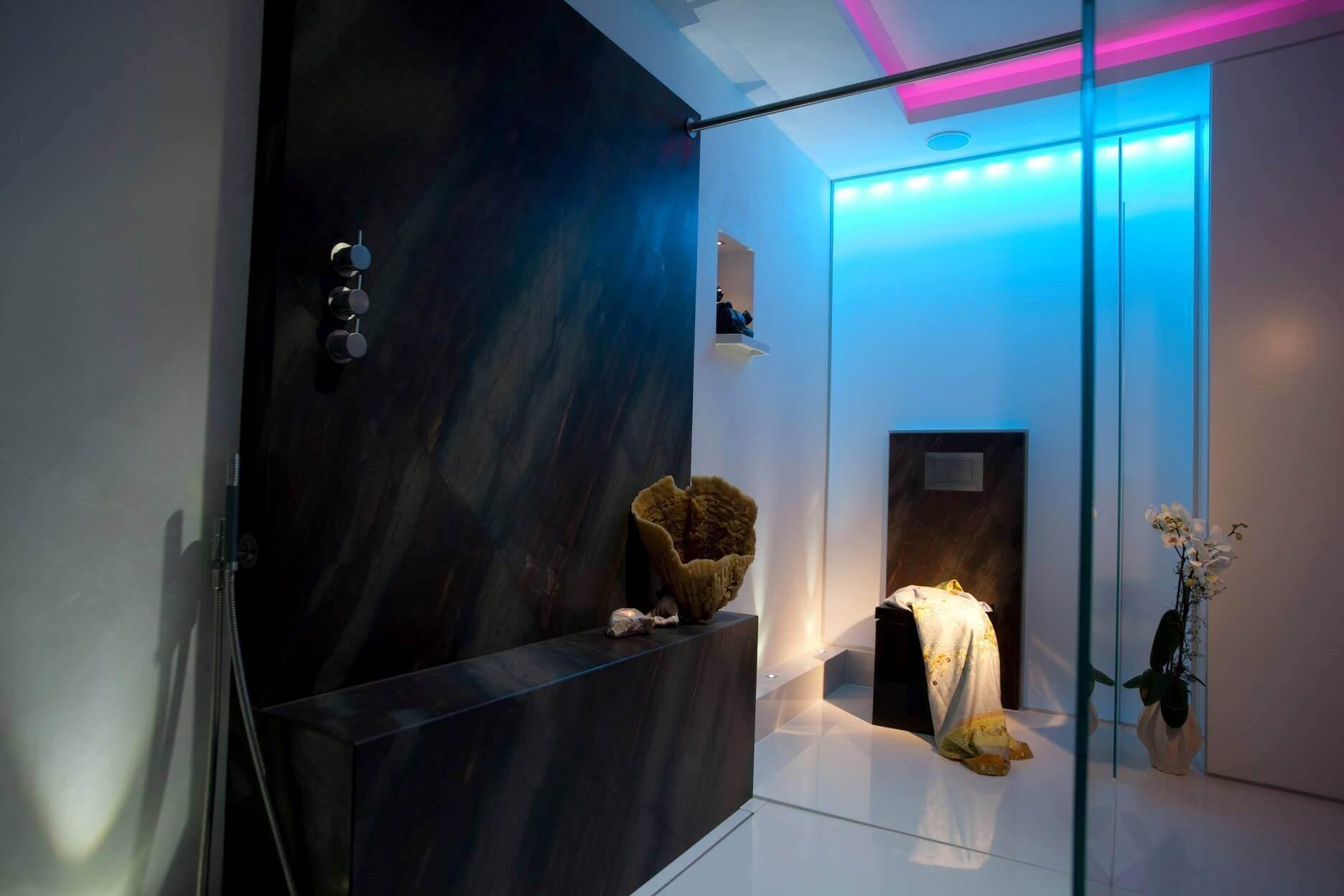 Die Bad Design Ideen vom Badplaner Torsten Müller umfassten für dieses Design Bad: Ein schwarzes WC als exklusiven Akzent im Bad eine beheizte Sitzbank in der Dusche zum barrierefreien Duschen Accessoires von Vola Edelstahl gebürstet für einen modernen Eindruck indirekte Beleuchtung durch Lichtvoute und LED RGB hinter einer Wand- und Deckenbespannung schlichtes Baddesign in der Detailplanung, um ein meditatives Badambiente zu erzeugen. Die natürliche Leidenschaft für Stein kommt auch beim Badezimmer planen in dieser Badgestaltung durch die Verwendung des Naturmaterials von Antolini Verona, das auch in der Badezimmerausstellung der Bäder München zu sehen ist, zum Ausdruck. Ein harmonisches Badambiente im Design Bad entstand beim Badezimmer Gestalten durch das Bad Planen mit dem Antolini Naturstein, dessen Bad Muster für beste Badezimmer in der Bäderausstellung in Bonn, Köln, Bad Honnef oder Düsseldorf vorhanden sind. Anstatt auf eine Design Badewanne fiel die Wahl bei der Badezimmer Design Badgestaltung auf eine Dusche, die Golden Ager sicheres und barrierefreies Duschen ermöglicht. Die Dusch-Sitzbank aus braunem Naturstein aus der Bäderausstellung der Antolini Stone Gallery ist beheizt. Der großzügige Dusch-Bereich im Designer Bad wurde mit 13 Millimeter starken Sicherheitsglas abgetrennt. Eine moderne Vola Kopfbrause verspricht entspannte Momente im Komplettbad unter dem vitalisierenden Wasserstrahl. Best Ager Bad Design
