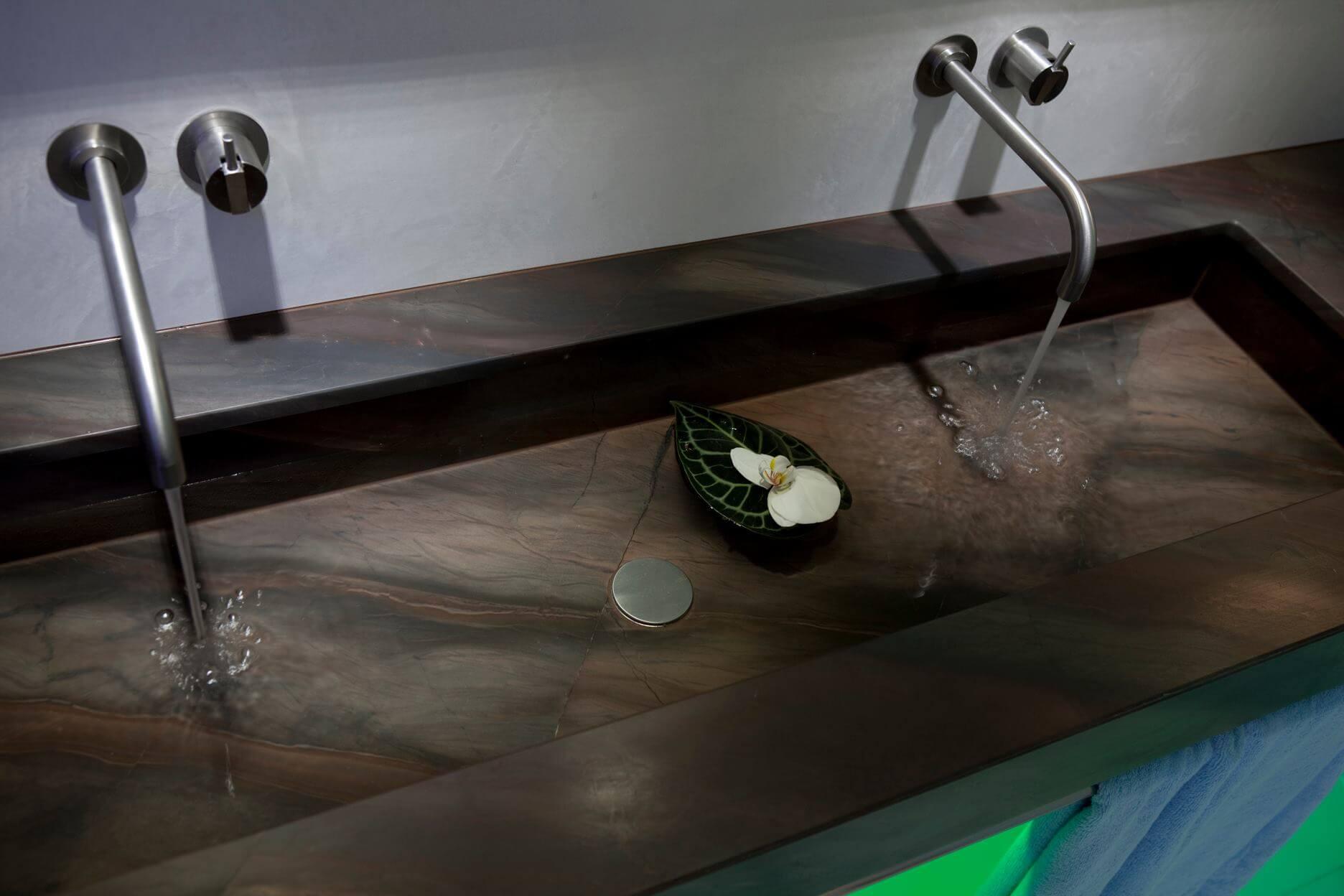 Das Badzubehör Design von Vola, das sich im Vola Handtuchhalter, der Vola Armatur, dem Vola Badheizkörper und der Vola Kopfbrause manifestiert, orientiert sich an der industriellen Badkultur, die insbesondere durch die indirekte Beleuchtung durch LED RGB hinter der Wand- und Deckenbespannung optimal zur Geltung kommt. Der Naturstein Waschtisch ist mit zwei schlichten Wasserhähnen von Vola Edelstahl gebürstet ausgestattet. Die Vola Armatur am Waschbecken harmoniert mit dem dazu passenden Vola Handtuchhalter. Für ein angenehmes Raumklima im Designer Bad sorgt der unauffällige Vola Badheizkörper, der beim Badezimmer planen selbstverständlich mitberücksichtigt wurde. Das Licht im Bad spielt auch hier eine entscheidende Rolle bei der Badezimmer Design Badgestaltung für exklusive Designbäder. Der Badezimmerplaner teilte bei der Umsetzung im Designerbad das Licht im Bad auf: LED Flächenlicht ist hier genauso zu finden wie Lichtvoute und eine hinterleuchtete Wand. Hinter der Wand- und Deckenbespannung verbirgt sich indirekte Beleuchtung, die mittels Lichtvoute für sanftes Licht sorgt. Einzelne LED RGB Spots setzen Highlights im Designerbad und ergänzen die indirekte Beleuchtung mittels Lichtvoute hinter der Wand- und Deckenbespannung um punktuelle Badezimmer Trends. Investitionszuschuss für altersgerechte bzw. barrierefreie Badumbauten - Das KfW-Programm 455 ist neu aufgelegt. Informationen zu den Fördermöglichkeiten sind auf der KfW-Internetseite oder über das KfW-Infocenter unter der kostenfreien Telefonnummer 0800 / 539 9002 erhältlich. Damit steht dem Badezimmer Design für die Sinne ab sofort nichts mehr im Wege. Und soviel sei versprochen alle Baddesign aus unserem Hause sehen nicht danach aus. Best Ager Bad Design