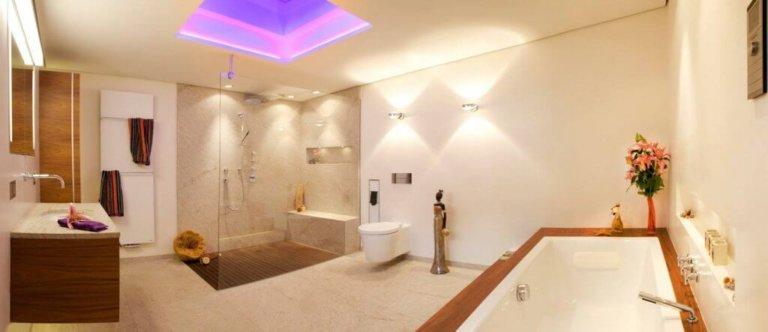 Ein exklusives Bad im ethnischen Stil Im Rahmen der Badsanierung wurde die bestehende Grundfläche des Design Bades auf 14,5 Quadratmeter vergrößert, um die bestehende Badarchitektur das gewünschte Luxusbad anzupassen. Dieses wurde vom renommierten Badplaner und Spa Designer Torsten Müller harmonisch in das Haus integriert und in vier separate Bereiche unterteilt. Bei dieser Bädergestaltung setzte der Baddesigner auf einen ganz speziellen Eyecatcher: Eine Design Badewanne für zwei Personen, die im Luxus Badezimmer auf einer Empore aus Teakholz thront. Gengenüber der Badewanne findet man im stilvollen Komplettbad die wandmontierte Toilette und eine bodengleiche Erlebnisdusche, die die großzügige Badgestaltung auf 1,20 mal 1,60 Meter fortsetzt. Diese zeichnet sich durch einen puristischen Teakholzboden und eine beheizbare Sitzbank aus.