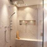 Bei dieser Bädergestaltung setzte der Baddesigner auf einen ganz speziellen Eyecatcher: Eine Dusche mit Sitzbank - kann sogar mit zwei Personen benutzt werden die im Luxus Badezimmer auf einer Teakholz Duschtasse die Sinne schweifen lassen.