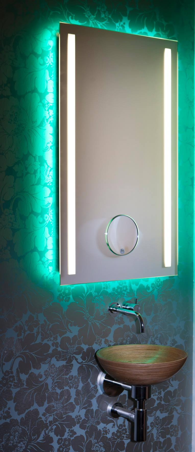 Inmitten der innovativen Einrichtungskonzepte für die gehobene Innenarchitektur sind Lichtspiegel mit farblichem Wechsel das revolutionäre Highlight. In einer einzigartigen Kombination aus technischem Raffinesse, Funktionalität und anspruchsvollem Design definiert Torsten Müller das Thema Lichtdesign-Spiegel neu. Der Schöner Wohnen Profi weiß, Licht und Farbe tragen wesentlich dazu bei, das Raumgefühl angenehm zu beeinflussen. In formaler Reduziertheit fokussiert der farbliche Lichtspiegel den Blick auf sich. Auffällig ist das intelligente indirekte Beleuchtungskonzept, das stets für die individuelle Lebensfreude justierbar und bedienbar ist. Hochwertig und äußerst funktional ist auch die geeignete Bedienbarkeit für jede Generation von IPhone- und IPad-Geräten per IPhone App und durch die Einbindung in die Smart Home Technik somit auch der fortschreitenden Digitalisierung im Badezimmer angepasst. Individualität pur in unterschiedlichen Spiegel-Formaten, Beleuchtungsarten oder mit integriertem Kosmetikspiegel (mit 5- facher Vergrößerung ein perfekter Assistent bei der Rasur oder beim Schminken) sind realisierbar inkl. optimaler Gesichtsausleuchtung. Die LED-Lichtkomposition ist langlebig, der Stromverbrauch minimal. Der Lichtfarbenspiegel by Torsten Müller ist erhältlich in den vielfältigsten Größen und somit passend im Bad, Spa und Raumdesign und natürlich auch im Gäste WC einzusetzen.