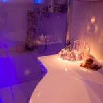 """Stimmungsvolle Lichtszenarien im Badezimmer Die Farbtherapie harmonisiert das körperliche und das seelische Wohlbefinden mit Hilfe von Farben. Diese verfügen über eine bestimmte Wellenlänge, die je nach Farbton einen entspannenden oder vitalisierenden Effekt aufweist. Die hinter einer transparenten Glaswand verborgene Regendusche mit LED Leuchten besitzt eine intuitiv zu bedienende Schaltfläche, auf der die einzelnen Impulse individuell eingestellt werden können. Auch eine Programmierung im Voraus erlaubt es in der Früh mit den Strahlen einer aufgehenden Sonne aufzustehen. In dem vorliegenden Projekt wurde der Colorshower der Firma KWS eingebaut, der über moderne Lichtelemente in der Kopfbrause verfügt. Vielseitige Funktionen, wie """"Wave"""", """"Sweep"""" und viele mehr lassen die LEDs in einem vorgegebenen Rhythmus aufleuchten, der je nach Wunsch beruhigt oder aufweckt. Auf der beheizten Sitzbank in der bodeneben gestalteten Dusche kann man sich eine Weile von dem Alltag entspannen und all den Stress hinter sich lassen, während von oben warme Wasserstrahlen herabfallen."""