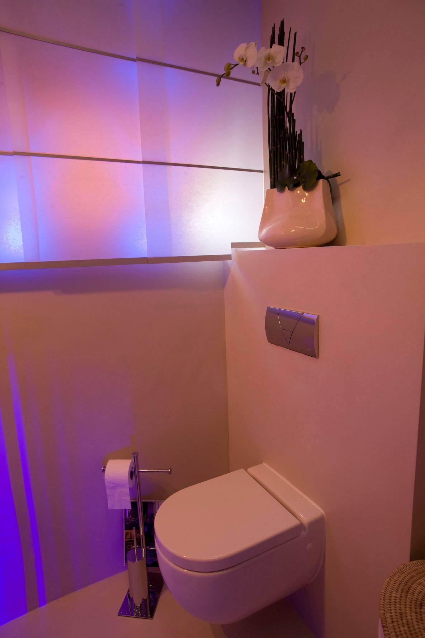 """Dass man aus einem kleinen Gäste Badezimmer sehr viel herausholen kann beweist der """"Schöner Wohnen"""" Designer Torsten Müller in diesem Projekt. Der Ansatz folgte der Idee, den vorhandenen Raum optisch zu vergrößern, weshalb er sich nach eingehender Bedürfniserhebung mit den Bauherren für eine Badsanierung ohne Fliesen entschied. Eine luftige Dusche mit Licht verwandelt das Gäste Badezimmer in eine Wohlfühloase in der eine entspannende Farbtherapie am Programm steht. Harmonie pur – Badezimmer fugenlos gestalten Stimmungsvolle Lichtszenarien im Badezimmer"""