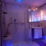 Gästebad mit Regenbrause Stimmungsvolle Lichtszenarien im Badezimmer Die Farbtherapie harmonisiert das körperliche und das seelische Wohlbefinden mit Hilfe von Farben. Diese verfügen über eine bestimmte Wellenlänge, die je nach Farbton einen entspannenden oder vitalisierenden Effekt aufweist. Die hinter einer transparenten Glaswand verborgene Regendusche mit LED Leuchten besitzt eine intuitiv zu bedienende Schaltfläche, auf der die einzelnen Impulse individuell eingestellt werden können. Auch eine Programmierung im Voraus erlaubt es in der Früh mit den Strahlen einer aufgehenden Sonne aufzustehen.