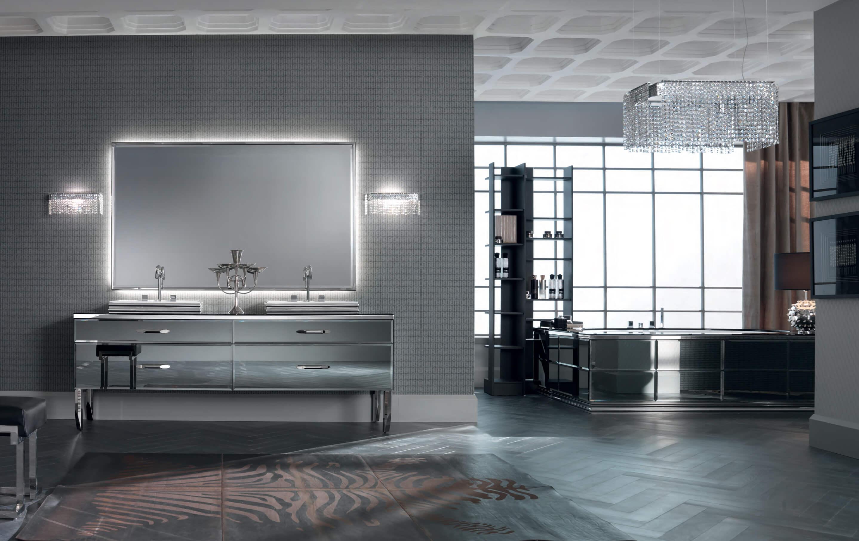 Ein Badezimmer wie vom Profi entsteht, wenn einfache Linien mit exklusiven Materialien verbunden werden. Diese Vision verwirklichten die Designer in der Ritz Kollektion: Inspiriert von klassischen Formen der Möbelstücke aus dem Goldenen Zeitalter wurden diese mit einem untrüglichen zeitgemäßen Finish in das 21. Jahrhundert befördert. Essentielle, eindrucksvolle Möbelstücke profitieren von der scheinbar nackten Linienführung. Geometrisch scharfe Paneele auf den Fronten der Waschtischunterschränke und im Inneren des Waschbeckens setzten ein starkes und selbstbewusstes Statement. Durch den Einsatz zeitloser Materialien, wie Marmor, Glas und Edelstahl entsteht ein luxuriöser Eindruck, der das Stilgefühl des Eigentümers und seine geradlinige Natur unterstreicht.