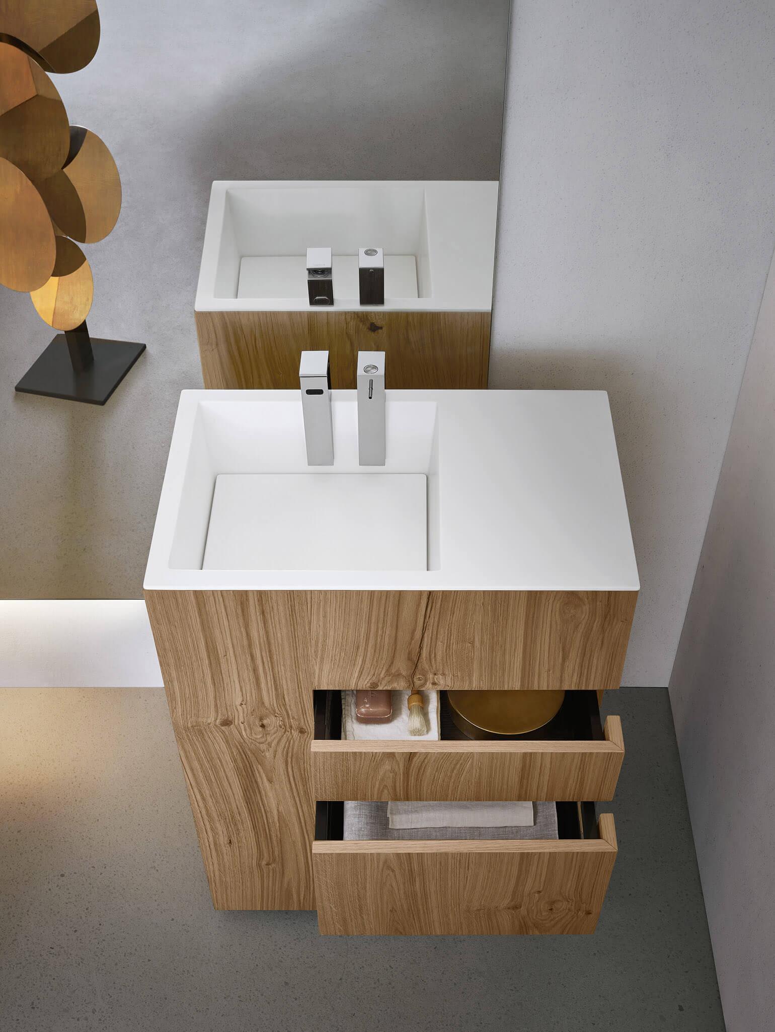 """Touch-Sammlung: die Geometrie von Volumina und die Eleganz der Materialien. Ein massiver Holzmonolith, kompakt im Volumen, funktional und einzigartig. Das ist Touch, die Waschtisch-Einheit von Noorth. Ein ausdrucksstarkes Element, bei dem eine strenge Geometrie seine Solidität und zeitgemäße Eleganz betont. Auf dem Bild die Eichenversion, mit dünnen Einschnitten, die die Form der Schubladen hochhalten und einen Umkreis in der einzigartigen """"Rinde"""" nachzeichnen."""
