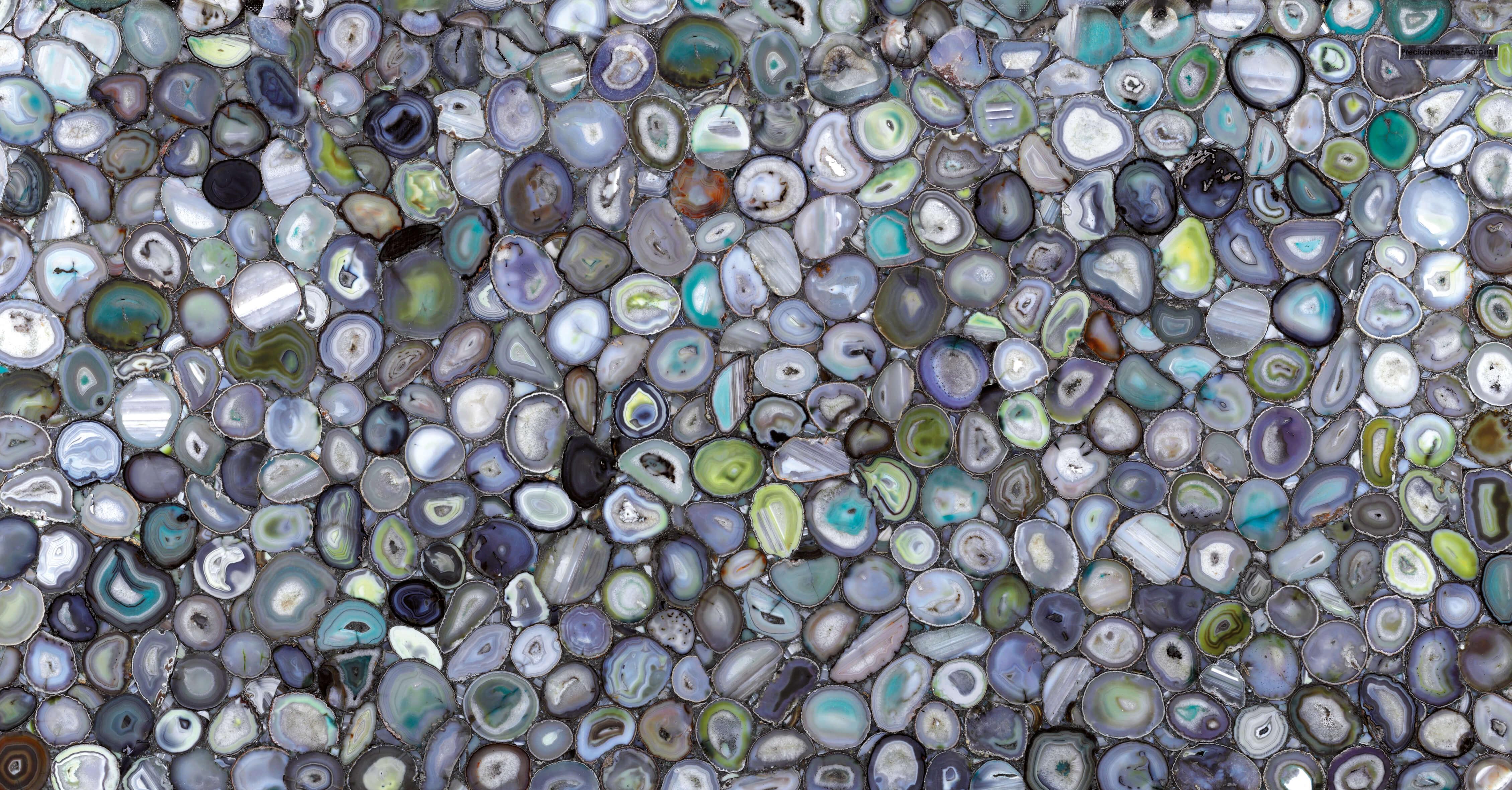 Grüner Achat Dieser Naturstein setzt alle Kräfte der Erde, ein Element, mit dem der Achat eng verwandt ist, in die Schönheit um. In Green Agate treffen die unendlichen Farbschattierungen aufeinander und kehren in eine Ära der Magie und des Mysteriums zurück, während die kraftvollen Brechungen eine einzigartige Alchemie schaffen, die die Umgebung umgibt und harmonisiert. Dieses Material erzeugt Atmosphären, die wie Geschenke von fernen Sternen auf Kristalltropfen wirken. Die Precioustone Kollektion von Antolini ist in der Lage, Aufmerksamkeit zu erregen und in einem Strudel aus Licht und Farbe zu tragen.