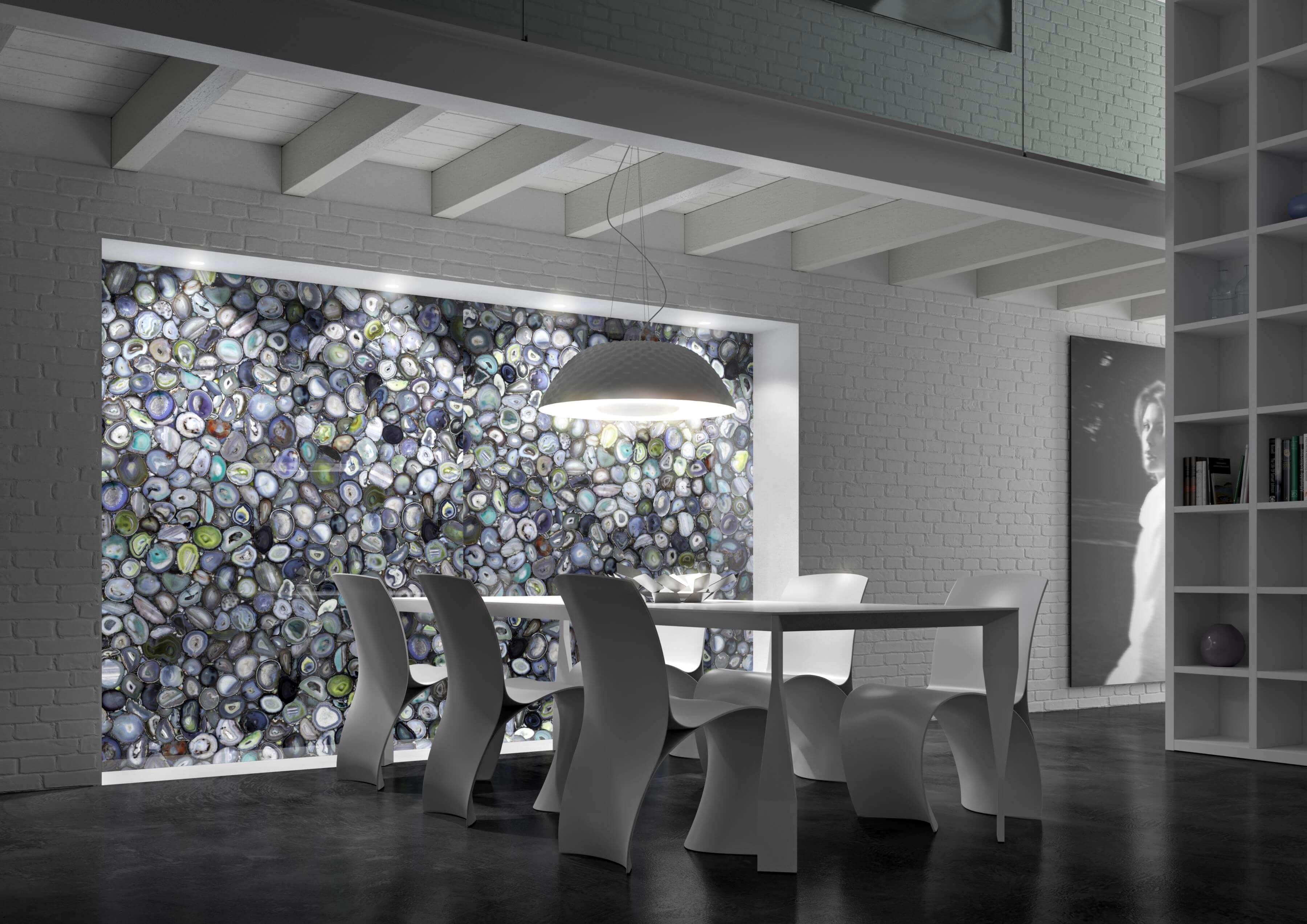 Grüner Achat ist das Protagonistenmaterial eines Wohnzimmers mit starken zeitgenössischen Akzenten, wo die doppelte Höhe Architektur interessante räumliche Perspektiven gibt. Die Schönheit des Natursteins trägt dazu bei, die starke Persönlichkeit dieser Umgebung zu schaffen und schafft eine Balance zwischen Überschwang und Minimalismus, Luxus und Einfachheit. Im Wohnzimmer in eisweißen Farbtönen kontrastiert der Reichtum der Wand aus grünem Achat - charakterisiert durch schillernde, helle Grün-, Blau-, Violett- und Grautöne in verschiedenen Farbtönen - mit der formalen Wesentlichkeit insgesamt. Der schillernde Effekt der Farben der Wand dieses herrlichen Antolini-Materials ruft kristallines Wasser und unberührte Räume hervor und schafft eine Atmosphäre von Wellness und ästhetischem Vergnügen.