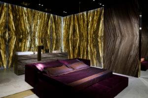 Natursteine Samtschönheit: ein Schlafzimmer mit Persönlichkeit Das von Alessandro La Spada entworfene Hauptschlafzimmer aus Sequoia Brown Antolini scheint in jahrhundertealtes Holz getaucht zu sein.