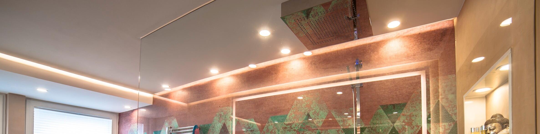 Lichtvouten für moderne Lichtkonzepte  Das Lichtkonzept wurde auf den modernen Lichtvouten aufgebaut, die für eine indirekte Beleuchtung sorgen, die die Seele auf die Pflege-, Reinigungs- und Schönheitsrituale im Luxusbad einstimmt.  Gemeinsam mit den eingesetzten Licht-Vouten entstand ein stimmungsvolles Lichtszenario. Um die RGB Strips nicht in zu grellen Impressionen erscheinen zu lassen, ist innerhalb der RGB Strip eine zusätzliche weiße verbaut, um die Töne ein wenig pastelliger und sanfter werden zu lassen und damit das Ambiente des Raumes zu unterstreichen.  Die Spotlights  an der Decke vervollständigen die sanfte Lichtstimmung im Badezimmer der Teenager.