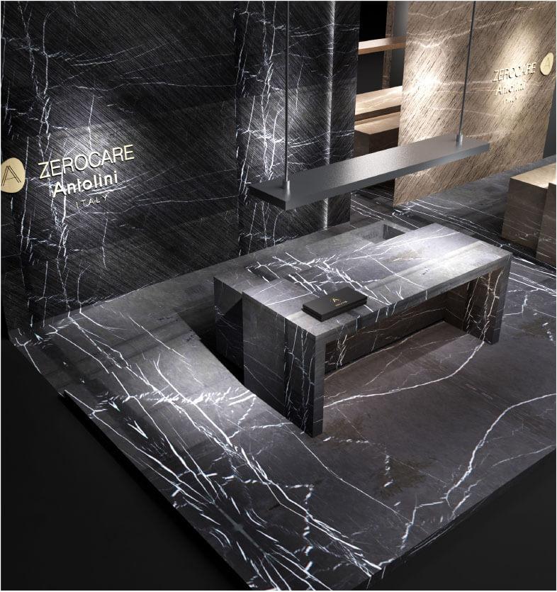 Verfeinerung und Innovation für Küchenräume mit imposanten skulpturalen Dimensionen Auf der IMM 2019 präsentiert Antolini ein beeindruckendes Display, das die Ausdrucksintensität von Naturstein steigert und sich gleichzeitig auf innovative Technologien konzentriert. Antolini, führend in der Herstellung von Naturstein und an der absoluten Spitze der Branche, nimmt an der IMM Cologne mit einer hoch entwickelten Installation des Designers Alessandro La Spada teil. Das harmonische und elegante Ausstellungsdisplay umfasst zwei Küchenblöcke, einer aus Bronze Amani und der andere aus Gray Stone: Wenn das erste Material mit seinen warmen, weichen, zarten Beige- und Cappuccino-Tönen fasziniert, die mit dunkleren Adern durchdrungen werden, überrascht das zweite Material durch seine flüchtige Persönlichkeit die verschiedene Grautöne mit schwer fassbaren weißen Adern abwechselt und ein abstraktes Design präsentiert, das so einzigartig ist, wie es nur die Natur bieten kann. Beide Küchenblöcke zeichnen sich durch eine lineare und geometrische Eleganz aus und verfügen über eine Schiebebrücke, die ihre Oberfläche verdoppelt und eine weitere verdeckte Oberfläche auf magische Weise enthüllt. Das Material von Amani Bronze und Grey Stone, das für die auf der IMM gezeigten Küchen verwendet wurde, wurde mit Azerocare behandelt. Azerocare wurde von Antolini patentiert und wurde speziell für Marmor, Onyx und weiche Quarzite entwickelt. Es handelt sich um eine revolutionäre Behandlung, die maximalen Schutz gegen Flecken und Ätzen durch Kontakt mit Nahrungsmitteln und sauren Substanzen garantiert. Azerocare wird von Antolini direkt auf die Plattenoberflächen aufgetragen und ist eine Garantie gegen mögliche Schäden, die durch die Verwendung von Produkten wie Wein, Kaffee, Öl, Essig, Tomatensauce und Fruchtsäften entstehen können, und ist daher die ideale Lösung für Oberflächen in Küchenumgebungen . Der elegante, graue Steinboden (Leder) vervollständigt das Gesamtbild und gibt der Installation