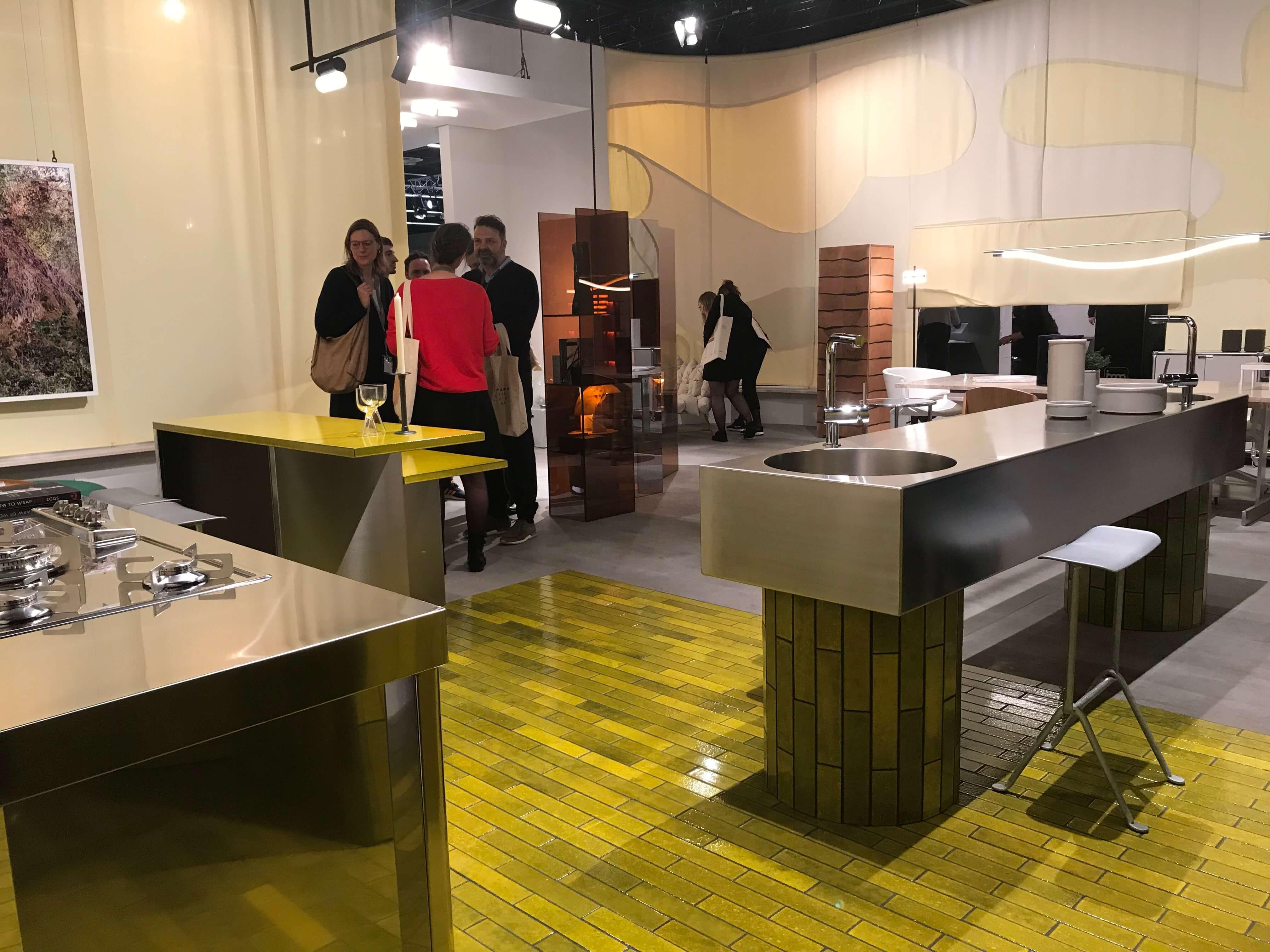 Küchen überraschen mit metallischen Arbeitsoberflächen im glänzenden und gebürsteten Look, die den dominierenden Steinplatten den Kampf ansagen