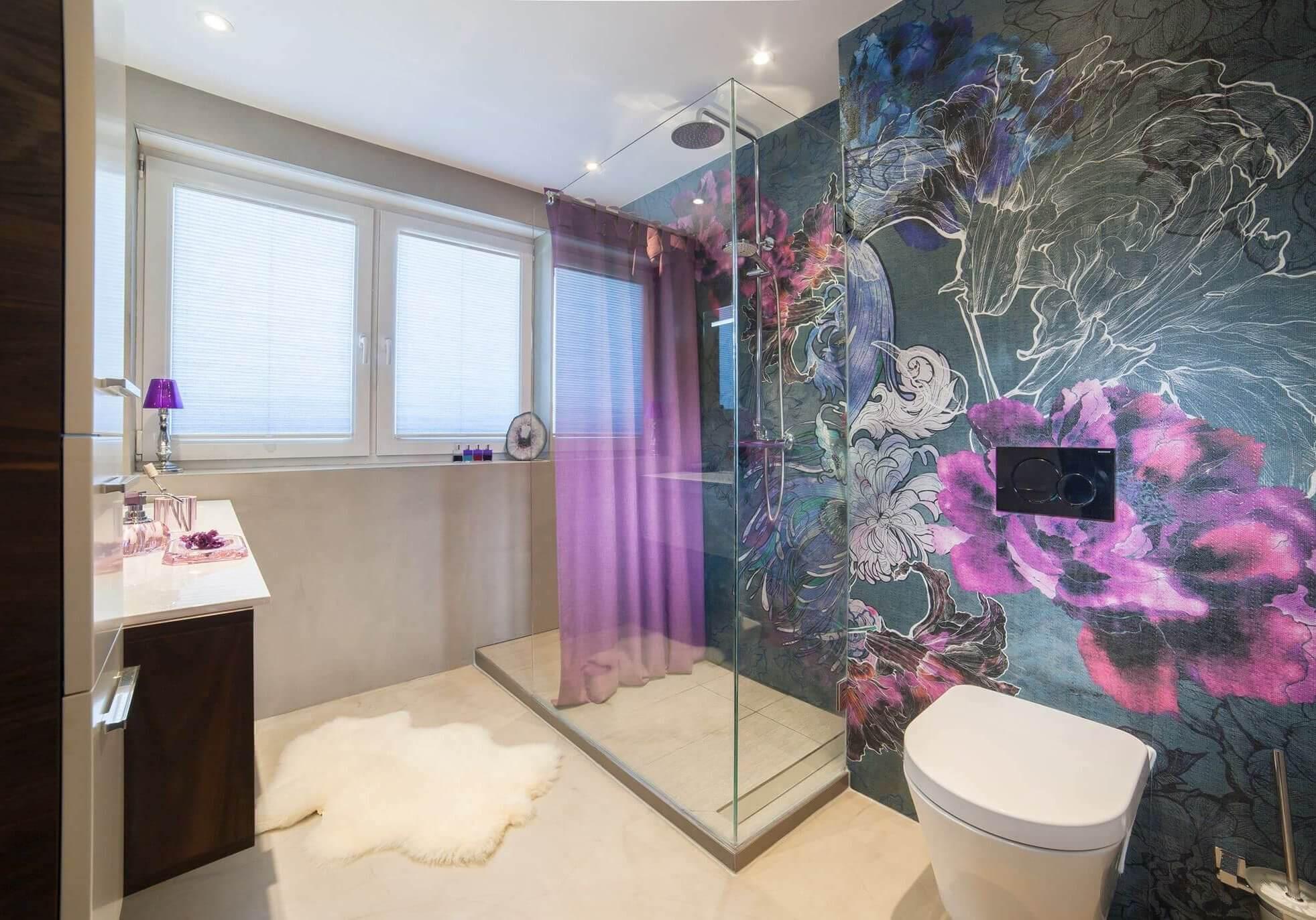 Der weiße Boden sorgt für viel Fläche, während die Wand mit der Feuchtraumtapete Stil und Extravaganz ins Bad bringt
